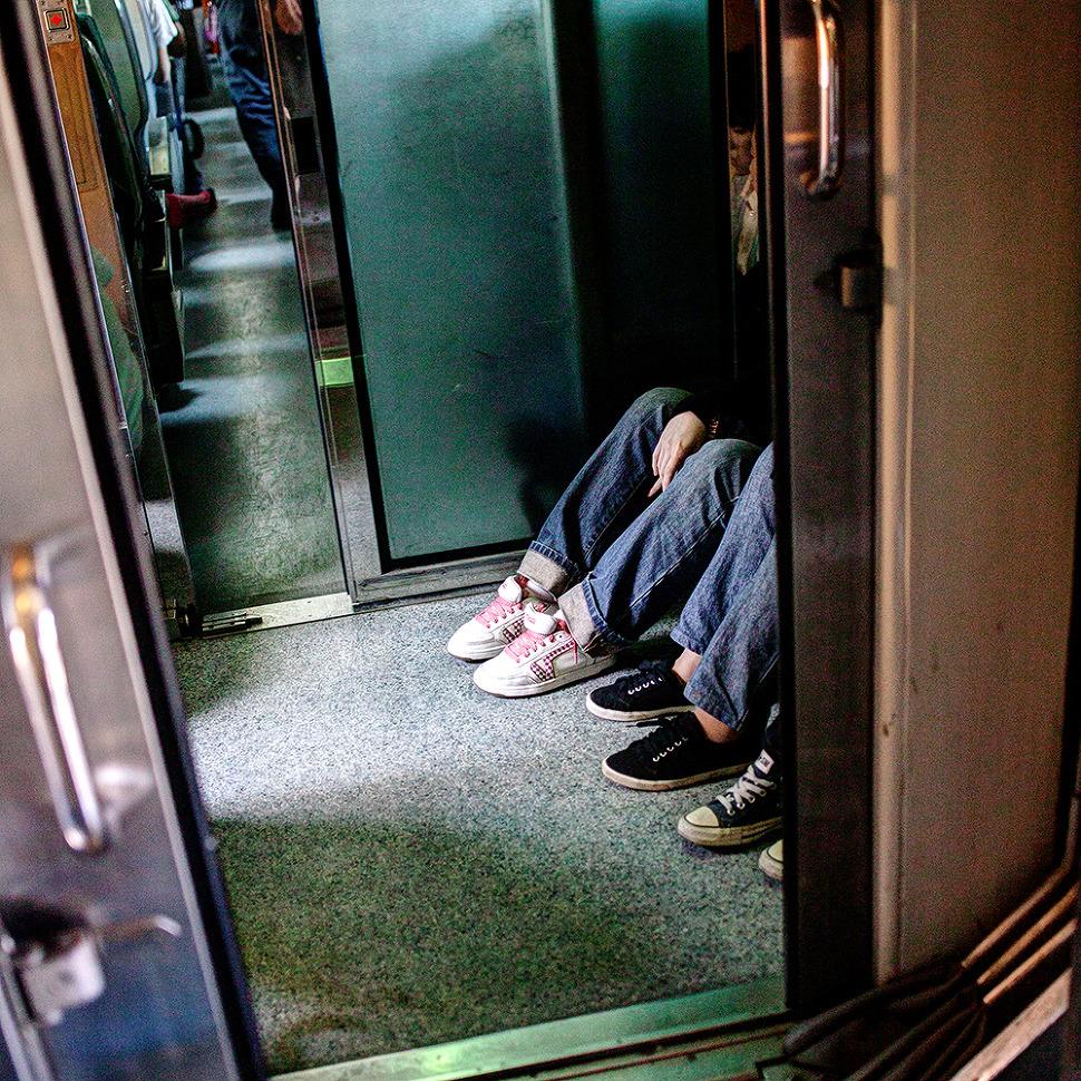 기차 통로에 앉아 재잘재잘 떠드는 아이들 사진.