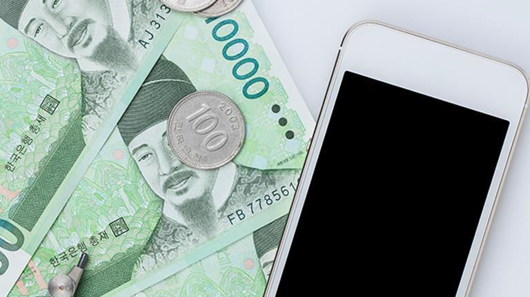 1만원권 지폐와 하얀 휴대전화